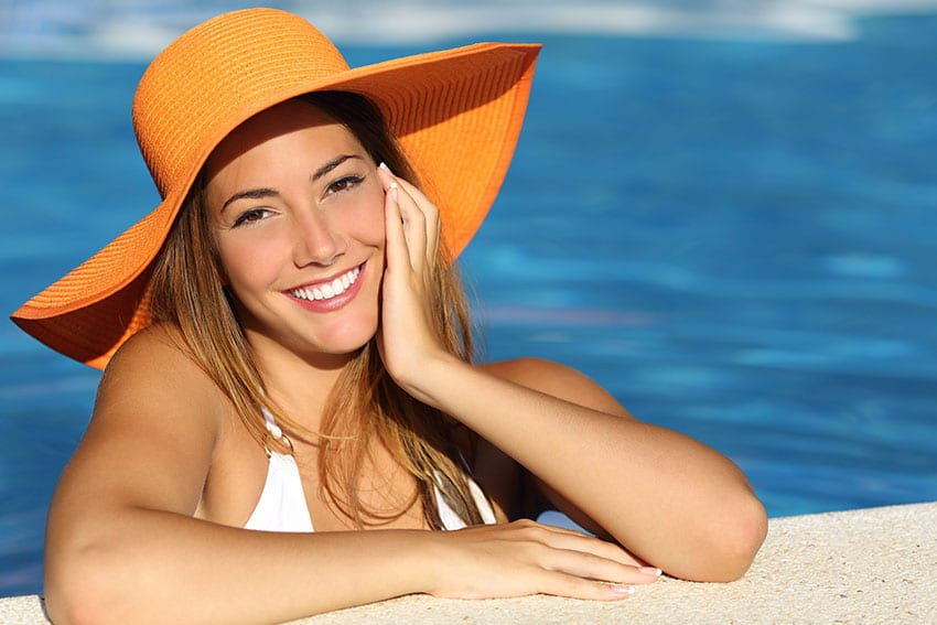 Attractive woman in large sunhat enjoys the pool