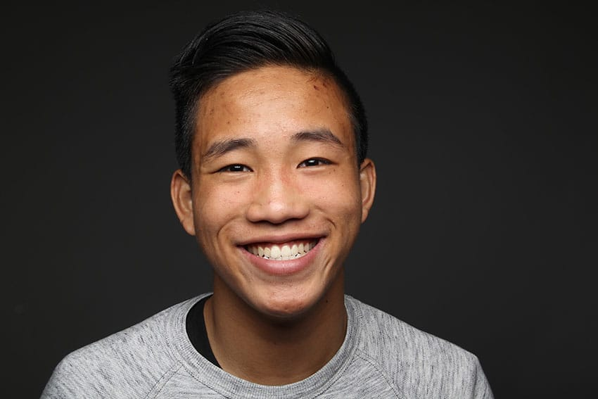 young Asian man shows off his wide smile