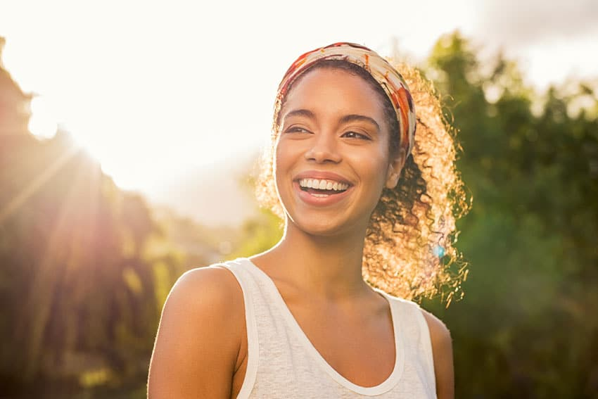 young woman with curly hair smiles while facing away from the warm sunshine