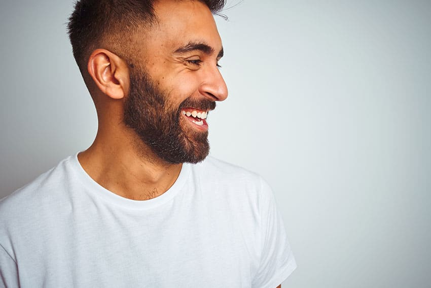 handsome man with a beard laughing at a joke